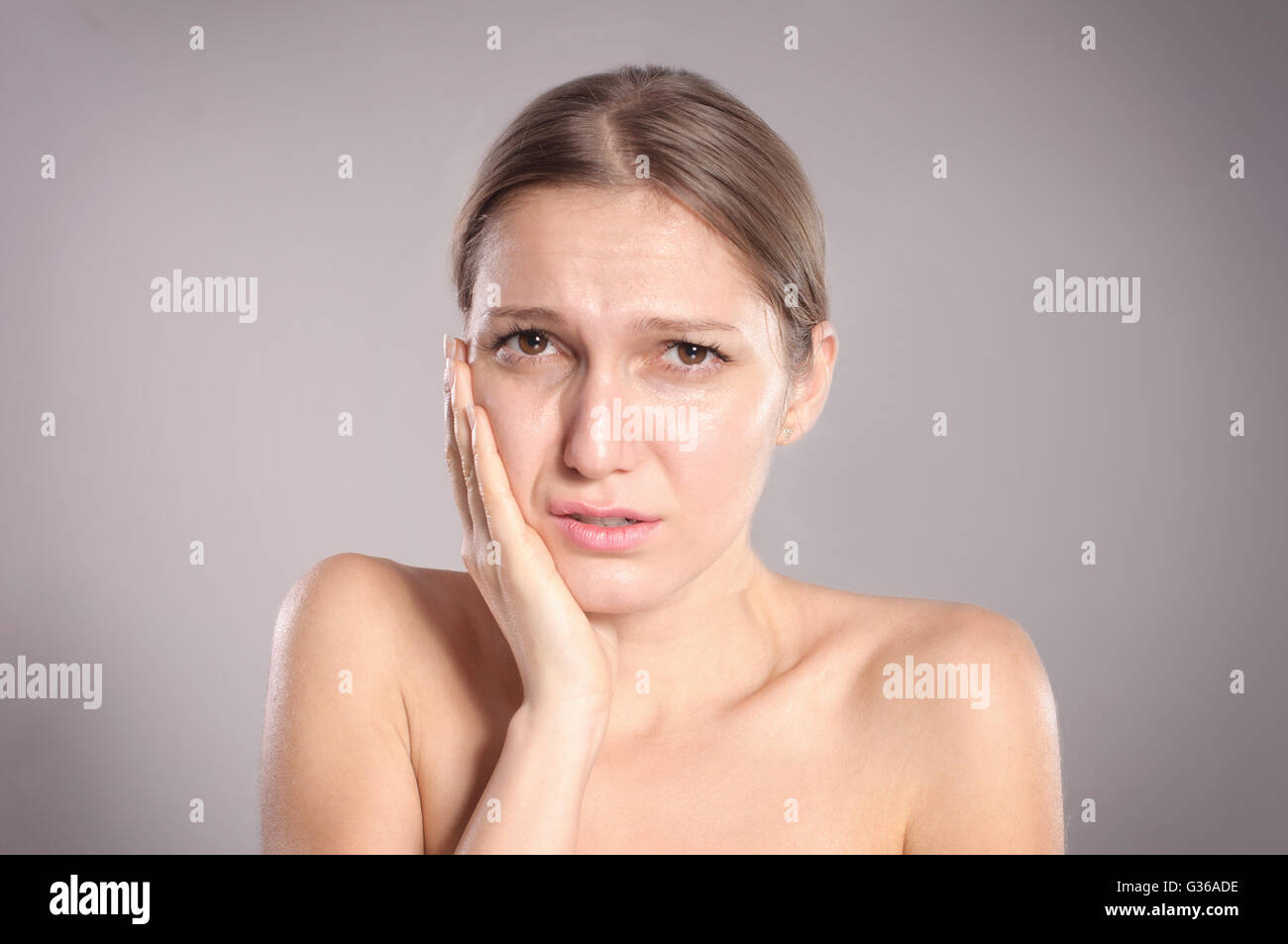 Portrait of young woman with toothache - Stock Image
