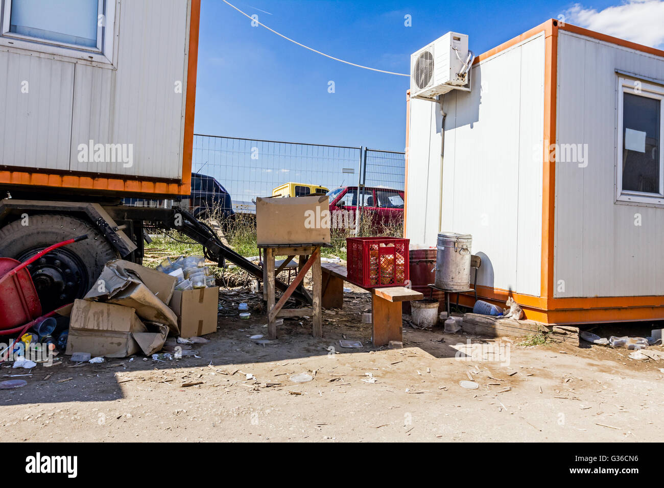 Workers place for eating among office containers near building site. - Stock Image