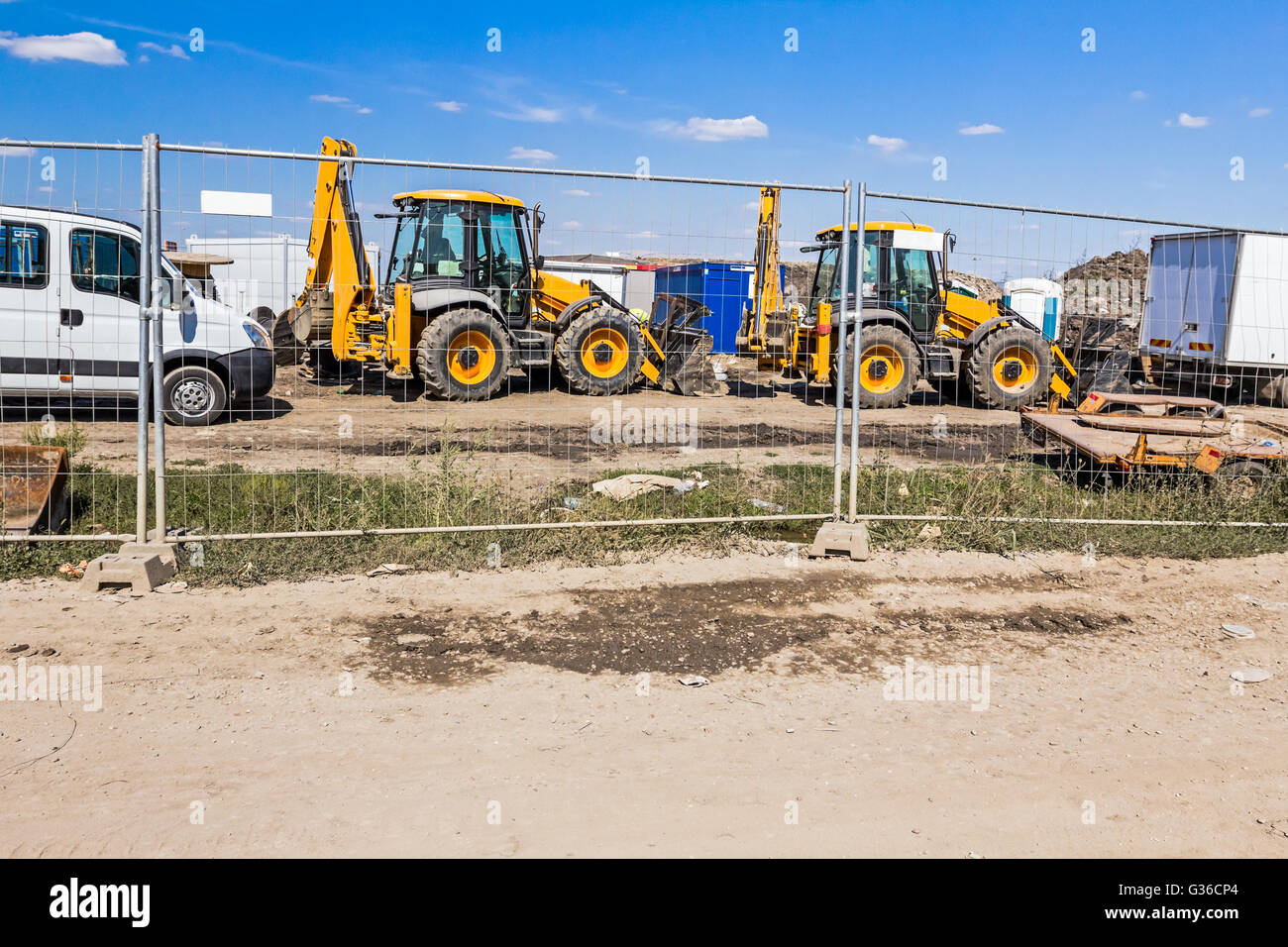 View on few excavators through a fence wire, parked at construction site. - Stock Image