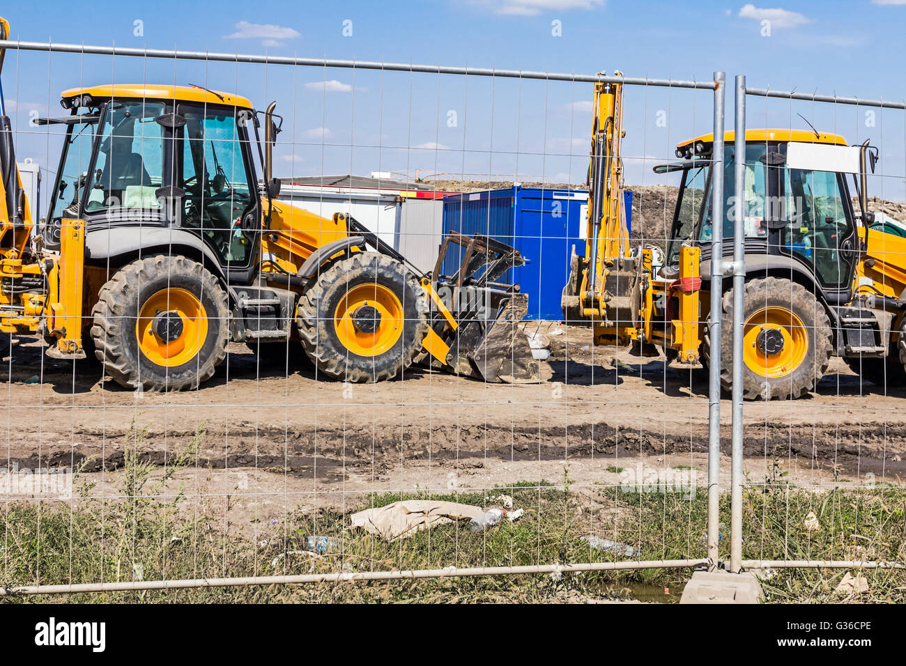 View on few excavators through a fence wire, parked at construction site. Stock Photo