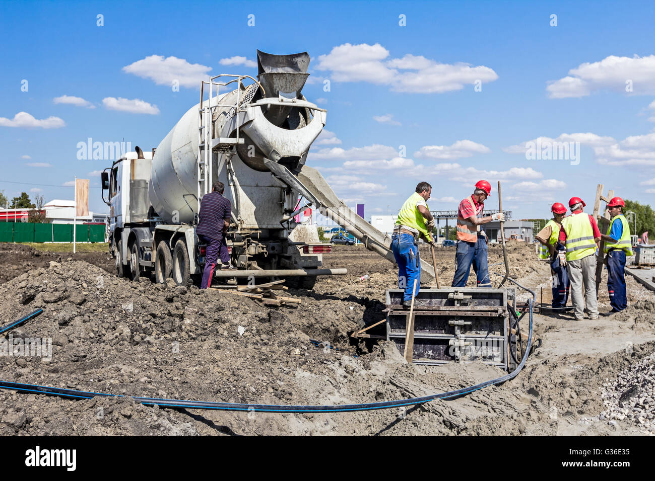 Workers at building site are pouring concrete in reinforced mold. Stock Photo
