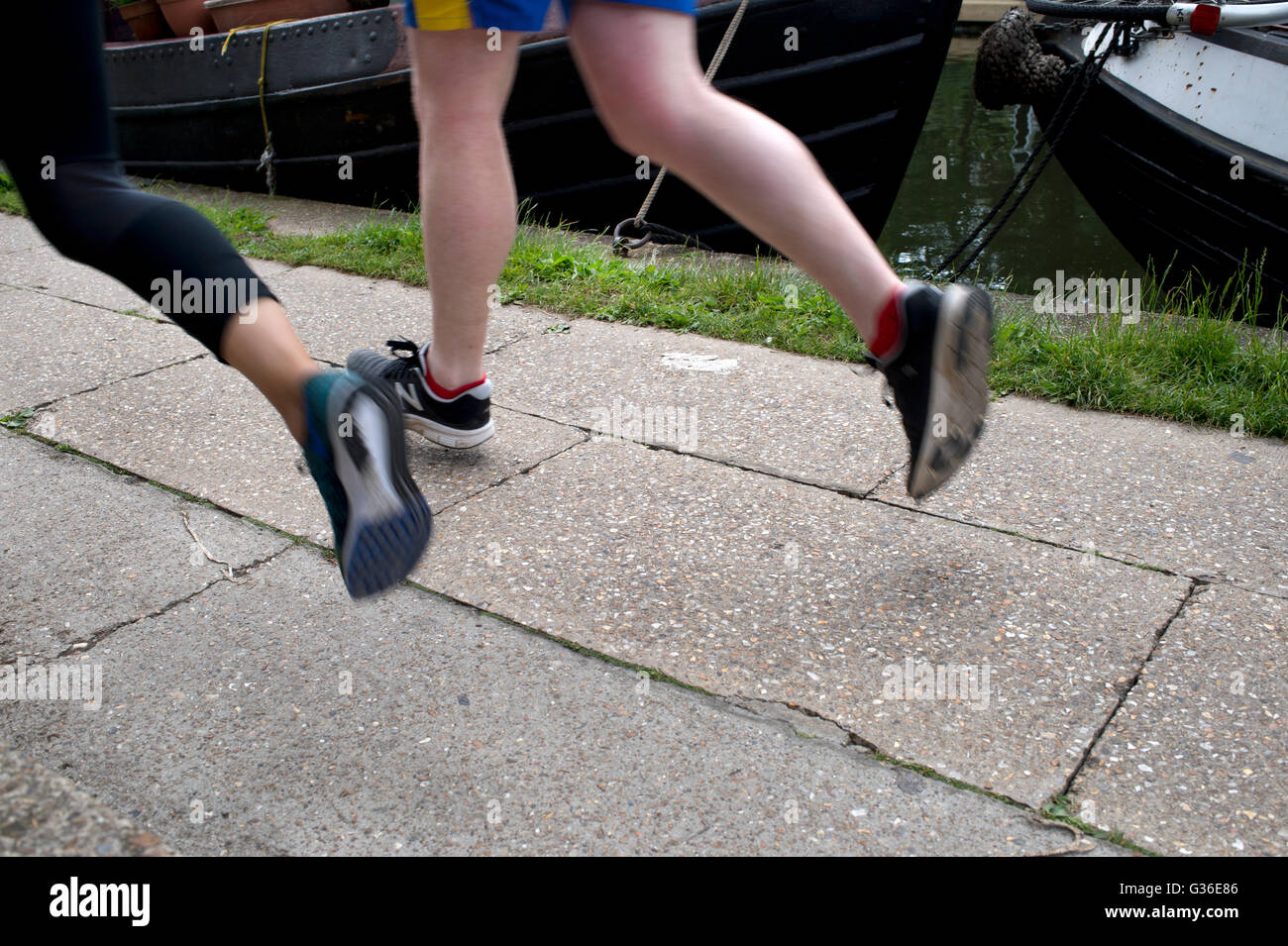 Hackney. Regents Canal. Runners on the towpath. - Stock Image