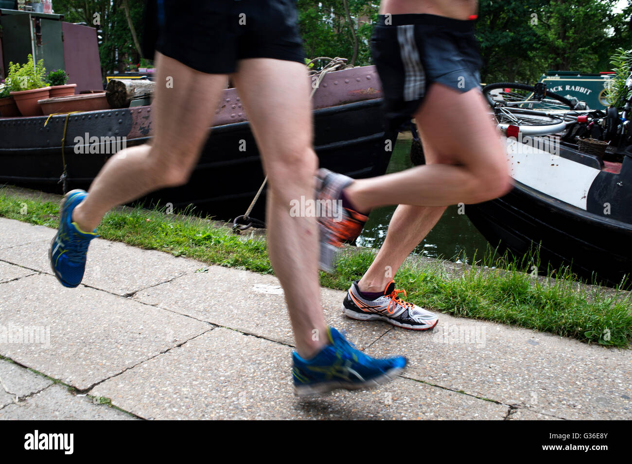 Hackney. Regents Canal. Two runners on the towpath. - Stock Image