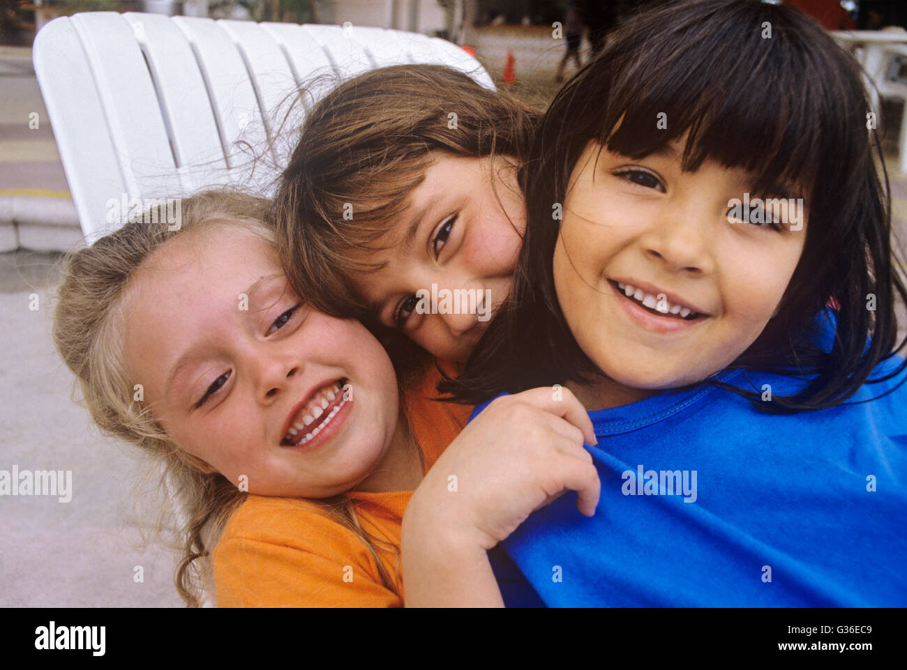 3 children hugging multi-racial group - Stock Image