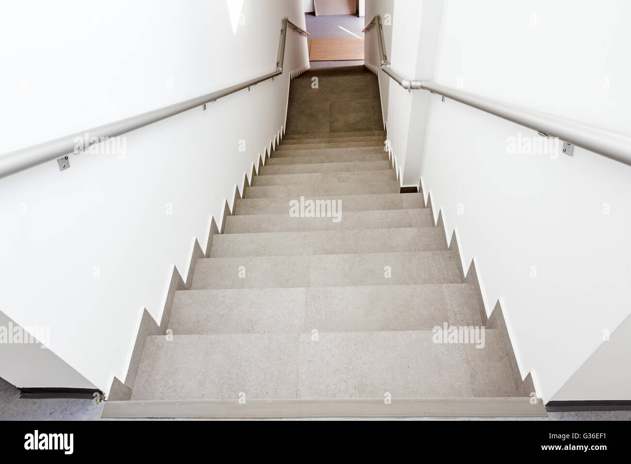 Stairway with metallic banister in a new modern building. Every building is required to have emergency stairways - Stock Image