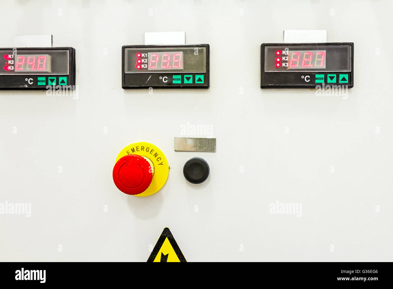 Electrical control panel containing has a digital temperature gauge with warning sticker and an emergency shutdown - Stock Image