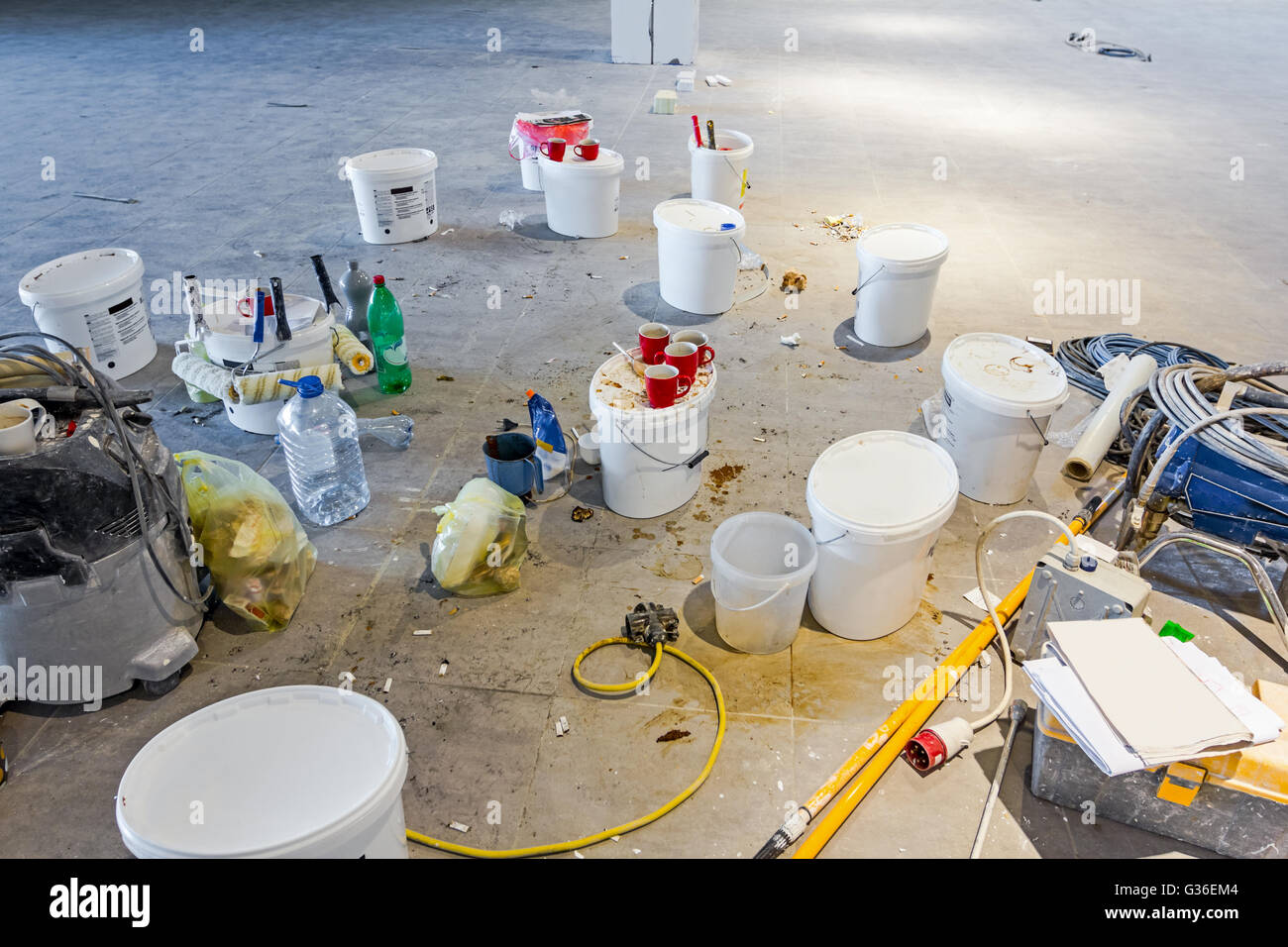 After pause workers have left messy leftovers on building site, painting cans. - Stock Image