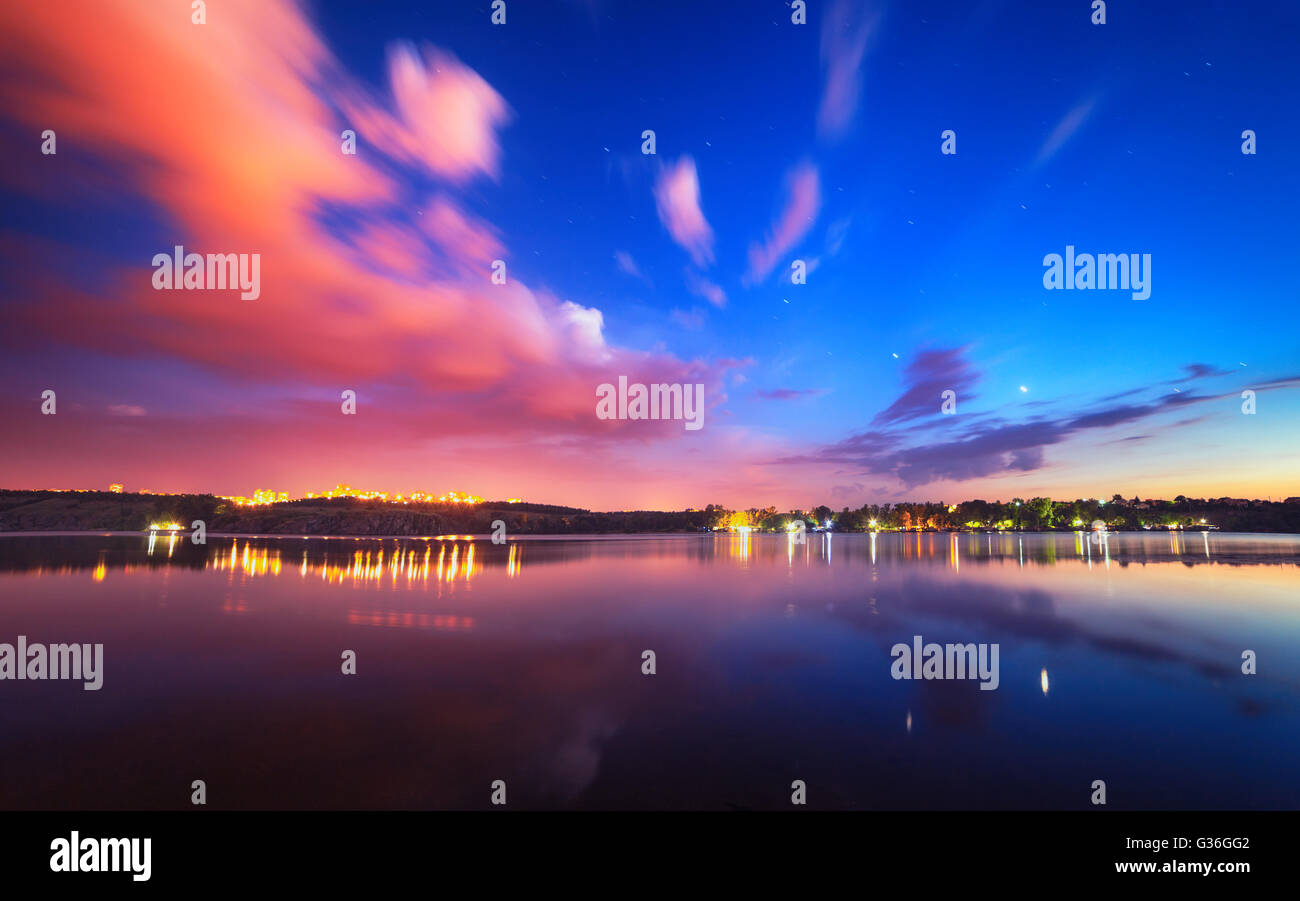 Colorful night landscape on the lake with blue sky and moving clouds reflected in water. Nature background - Stock Image