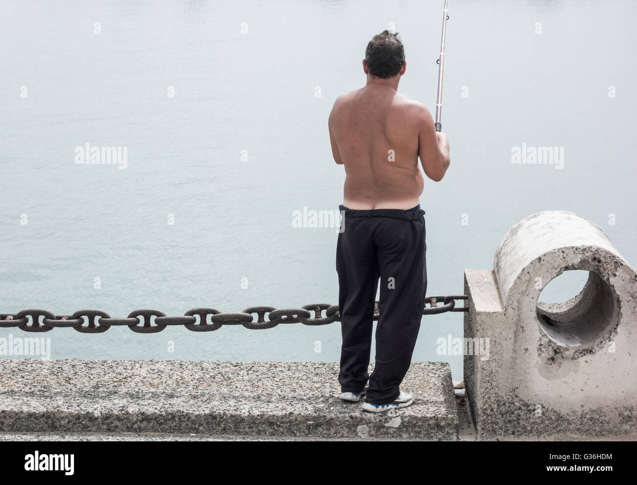 Man showing builders bum and marked tan line fishing from docks in Spain - Stock Image