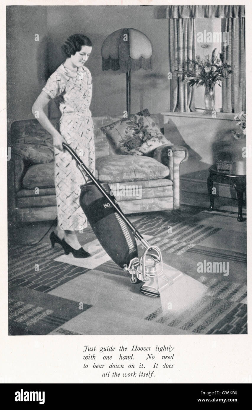 Woman hoovering in the 1930s     Date: 1930s - Stock Image