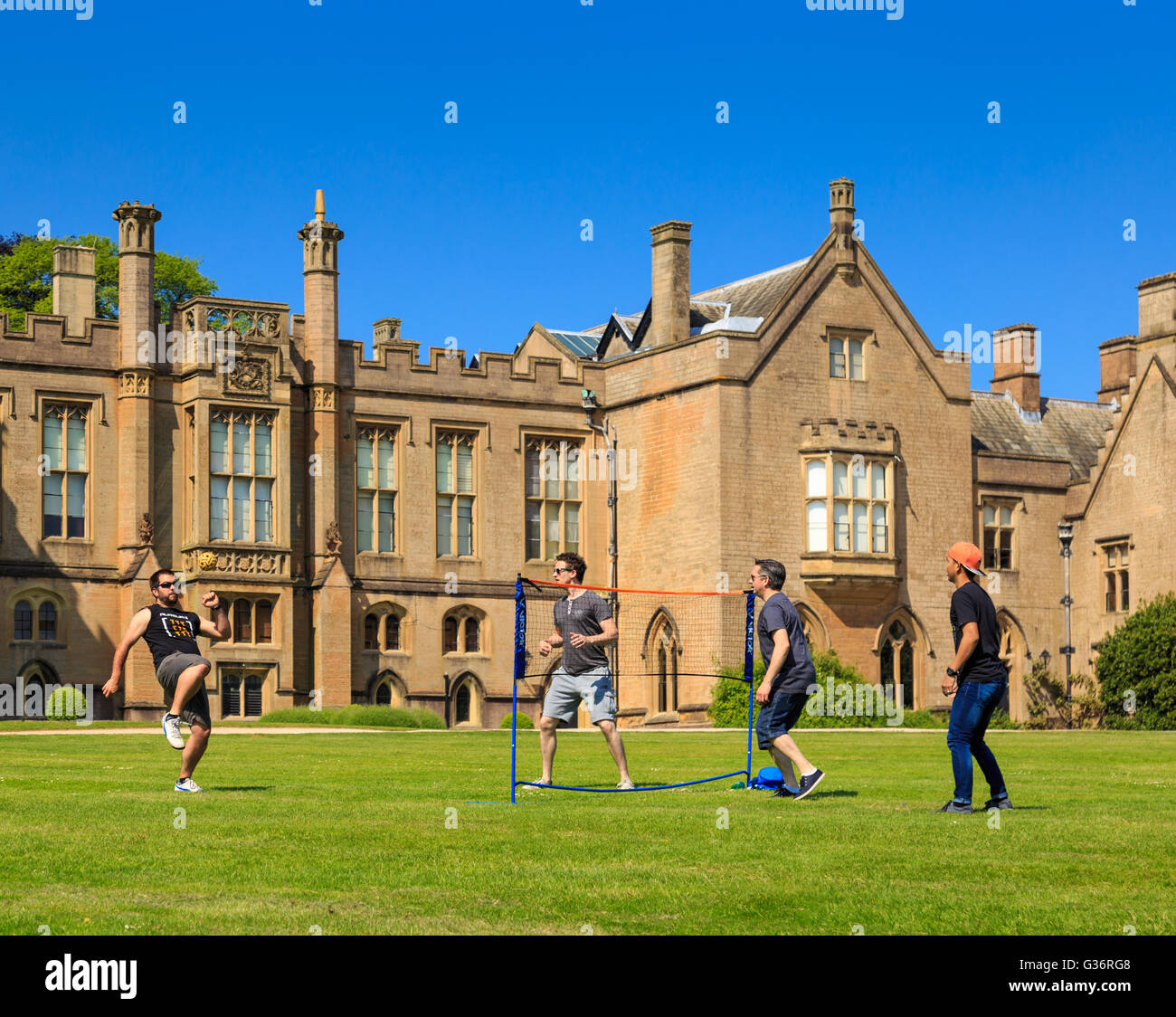 A group of young men playing Sepak Takraw (kick volleyball) on the lawn. At Newstead Abbey, Nottinghamsh - Stock Image