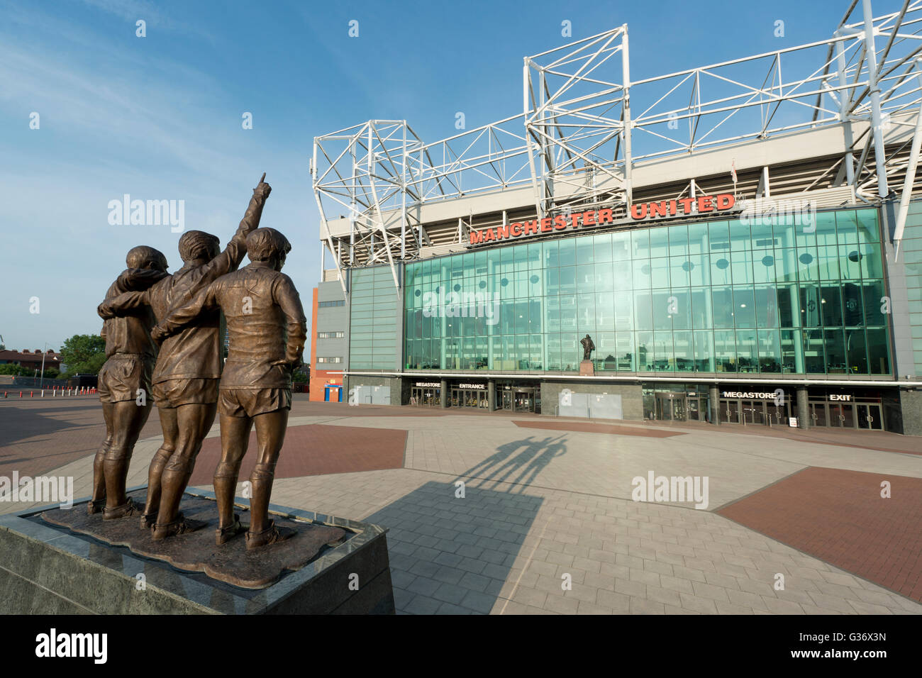 Old Trafford, the stadium of Manchester United Football Club, with the United Trinity statue on a sunny day (Editorial - Stock Image