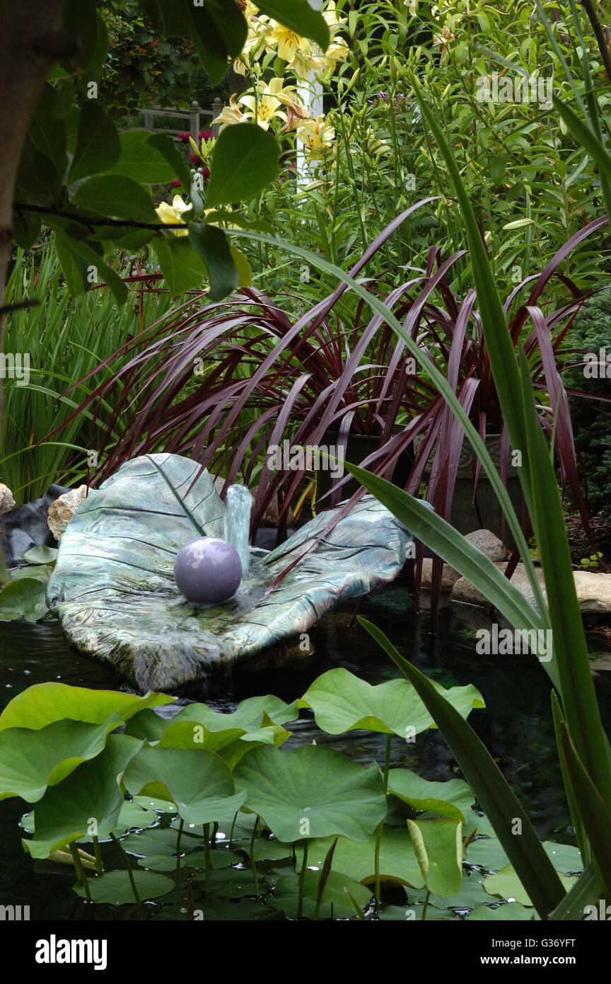 Cast concrete colocasia leaf used as water feature - Stock Image