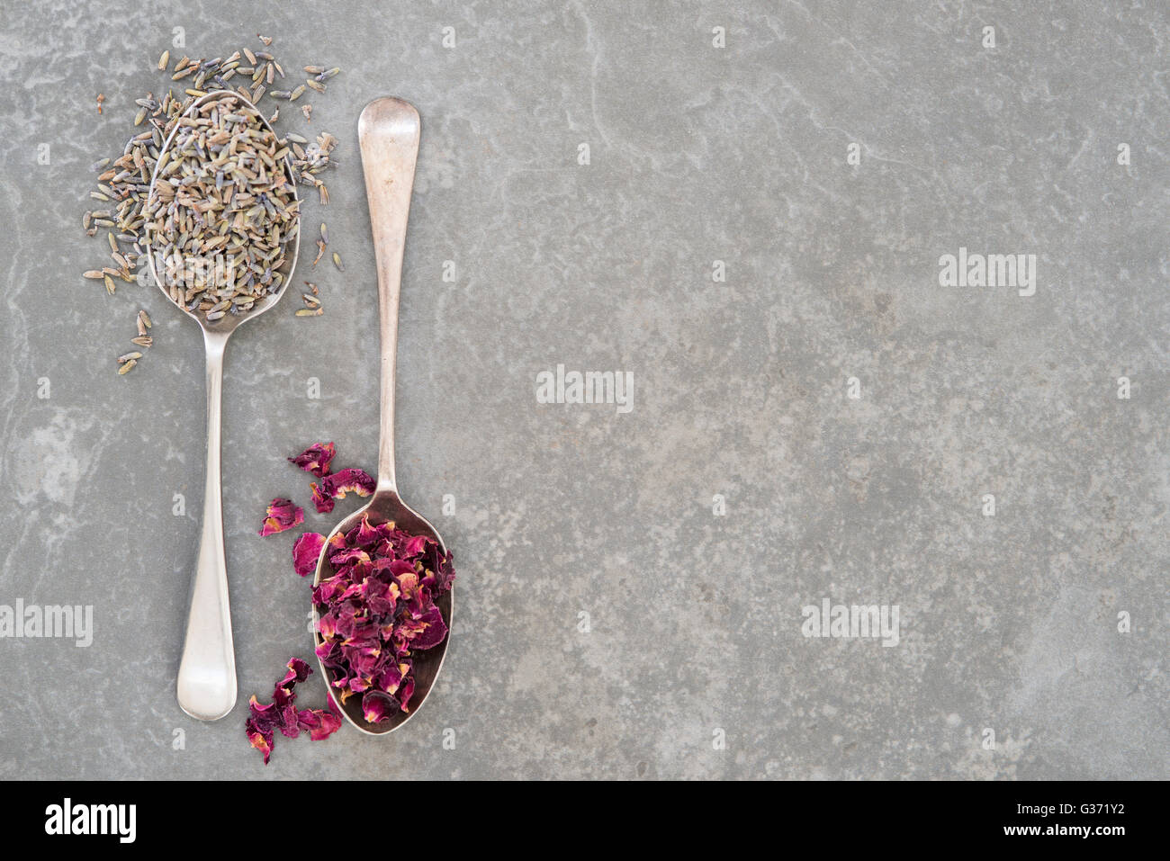 Spoonfuls of dried lavender and rose petals on stone surface with copy space - Stock Image