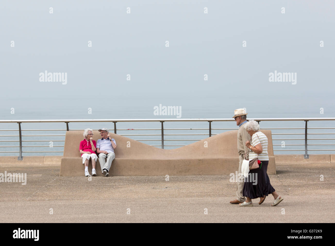 Warm weather at Blackpool , England.Enjoying the warm weather on the promenade.An elderly couple takes a stroll - Stock Image