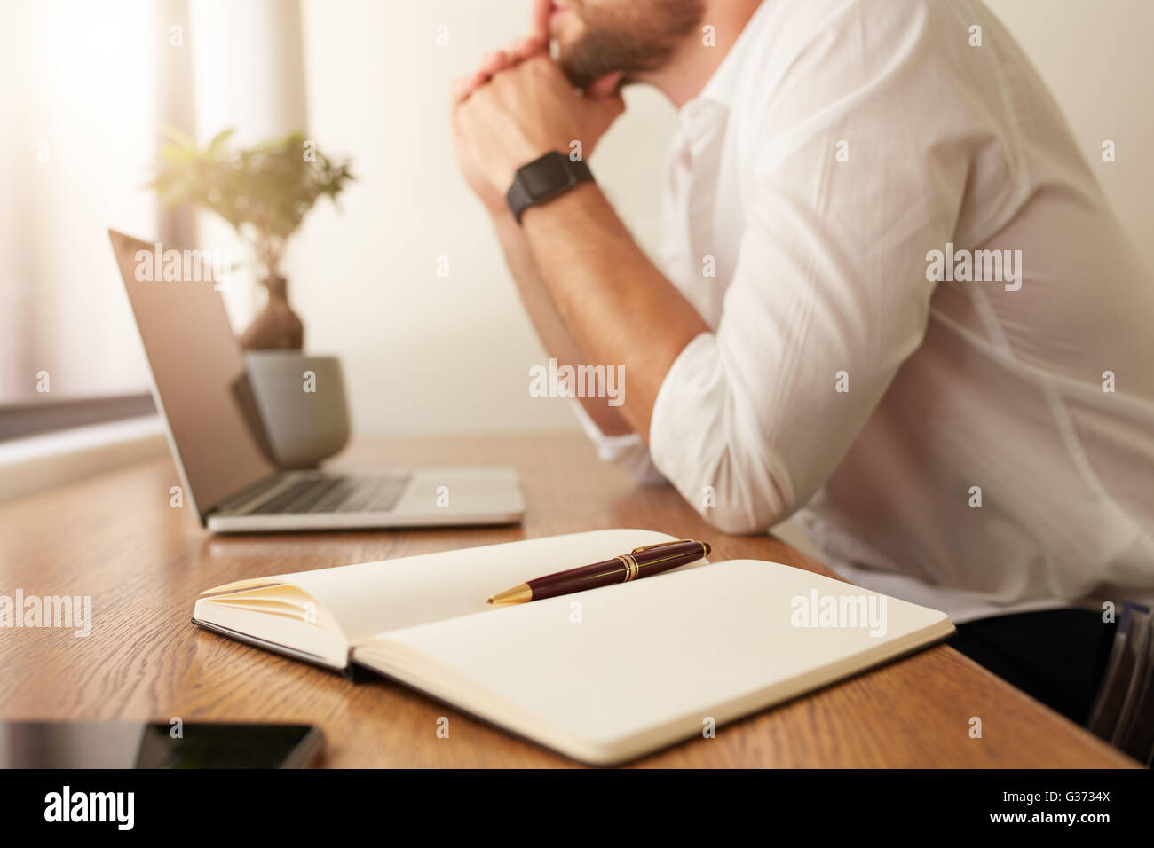 Image of personal organizer on table with businessman sitting in background. Diary with pen on table with man working - Stock Image