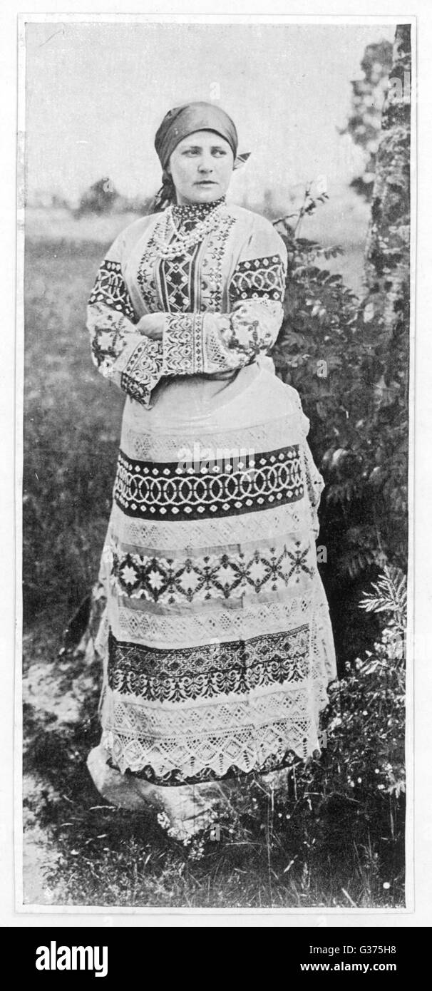 A Russian peasant girl in a  highly decorative full-length dress        Date: circa 1905 - Stock Image