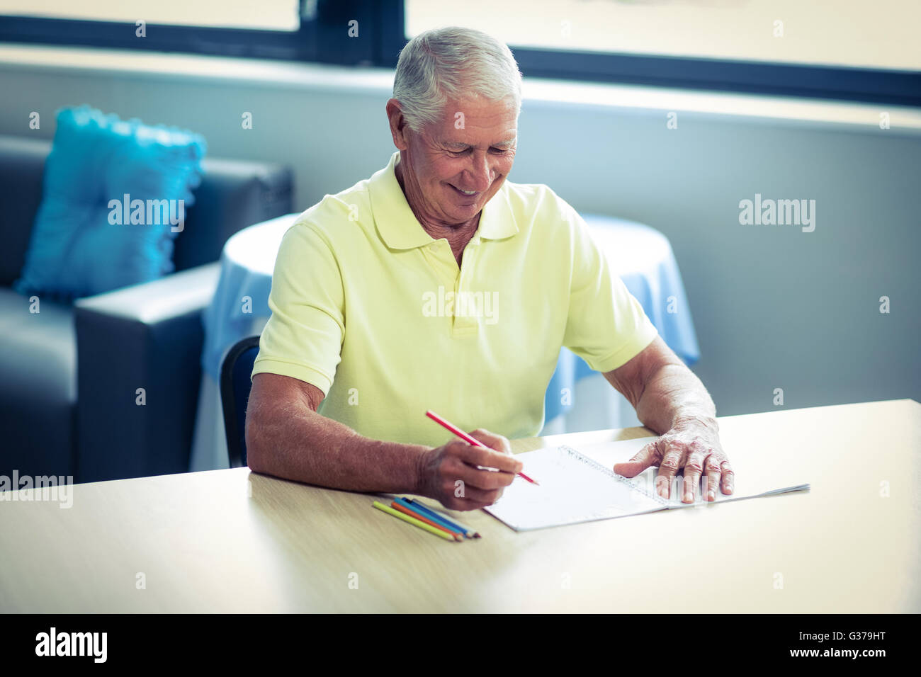 Senior man drawing with a colored pencil in drawing book - Stock Image