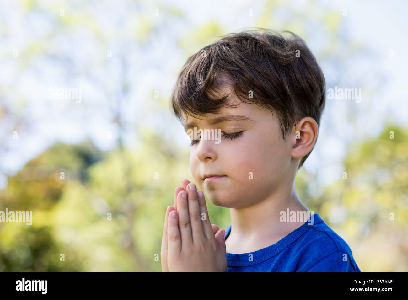 Boy praying with eyes closed - Stock Image