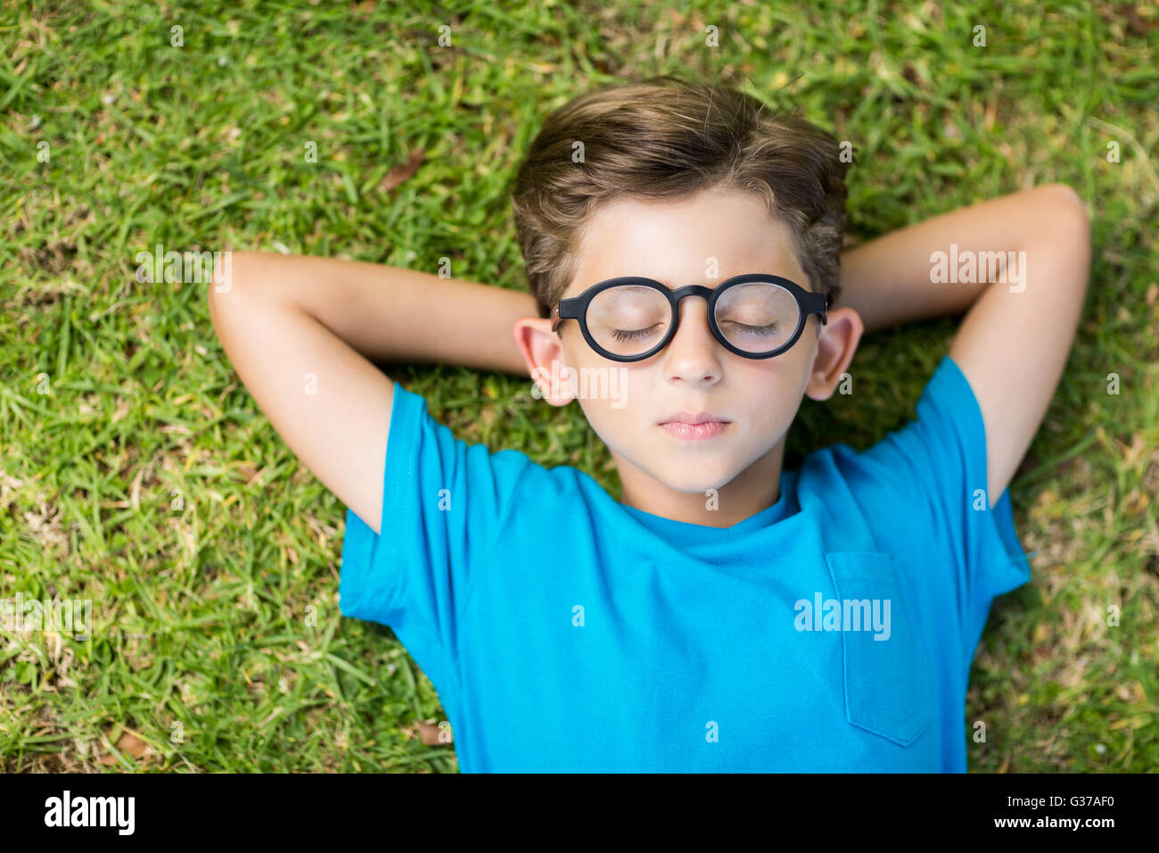 Young boy in spectacle sleeping in park - Stock Image