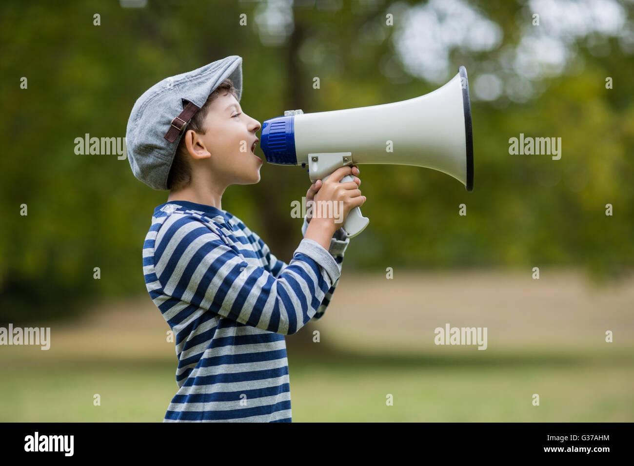Boy speaking on megaphone - Stock Image