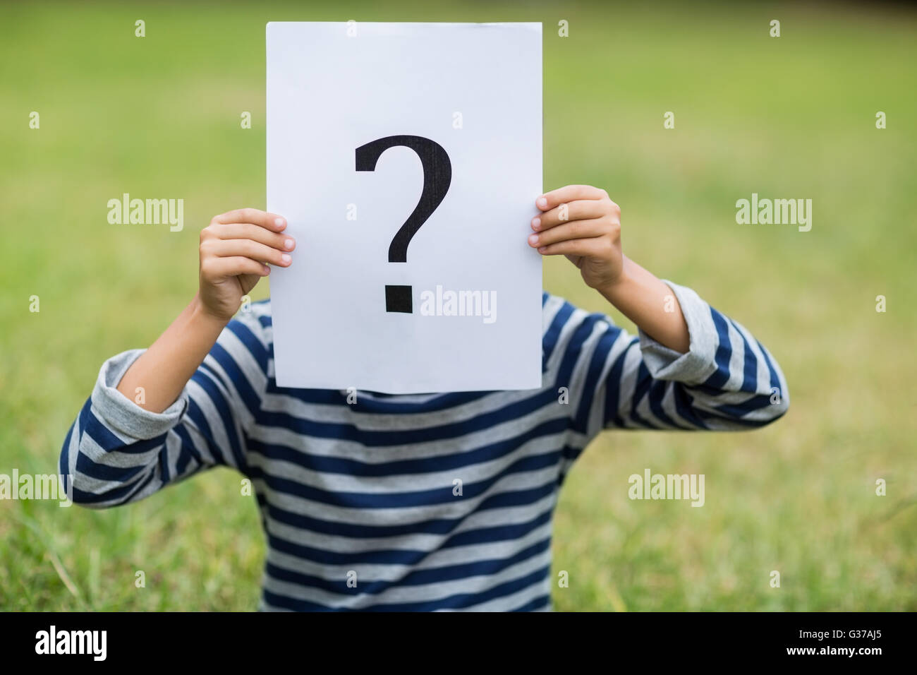 Boy covering his face with a placard that shows question mark sign - Stock Image