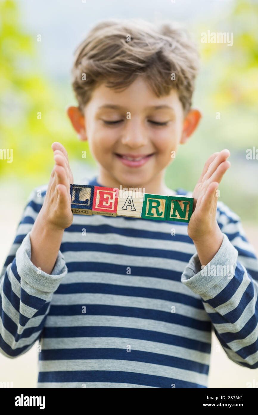 Boy holding blocks in park which reads learn - Stock Image