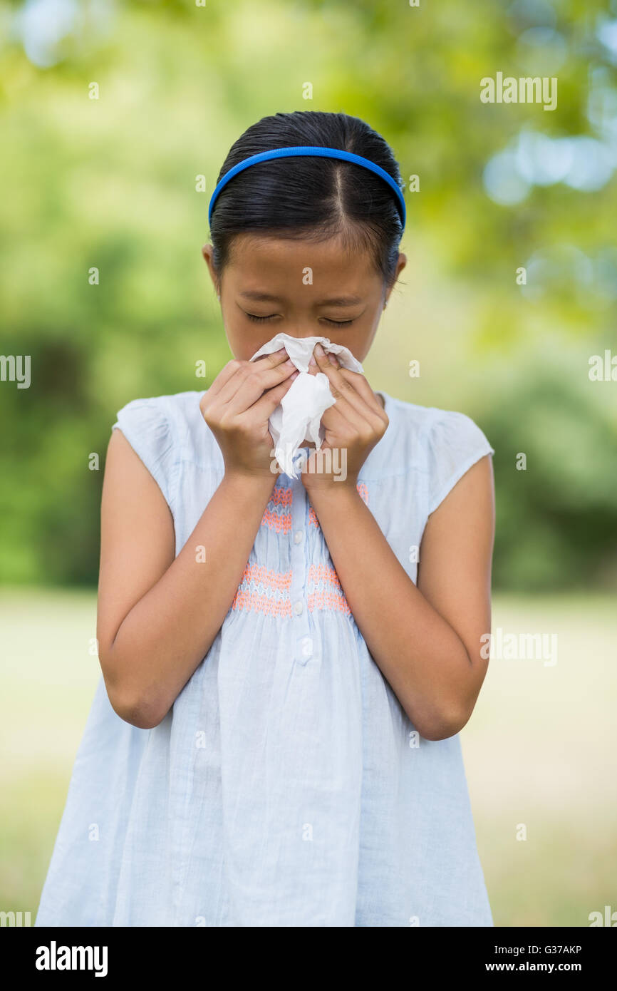 Girl blowing her nose with handkerchief while sneezing - Stock Image