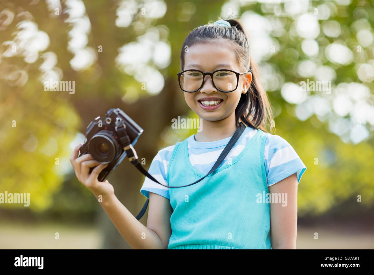 Portrait of smiling girl in spectacle holding a camera - Stock Image