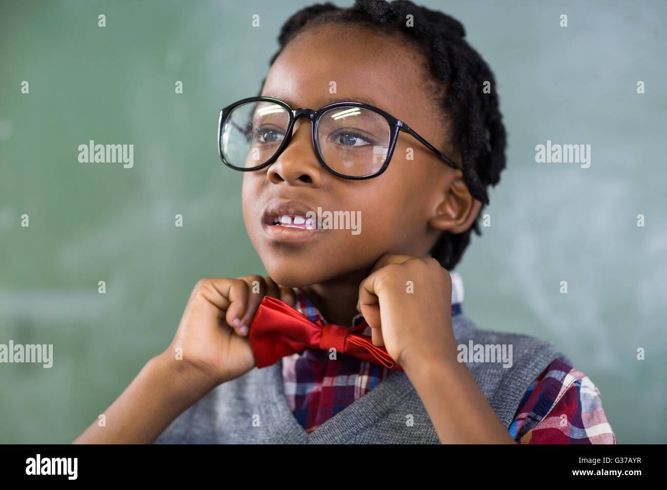 Thoughtful schoolboy adjusting a bow tie in classroom - Stock Image