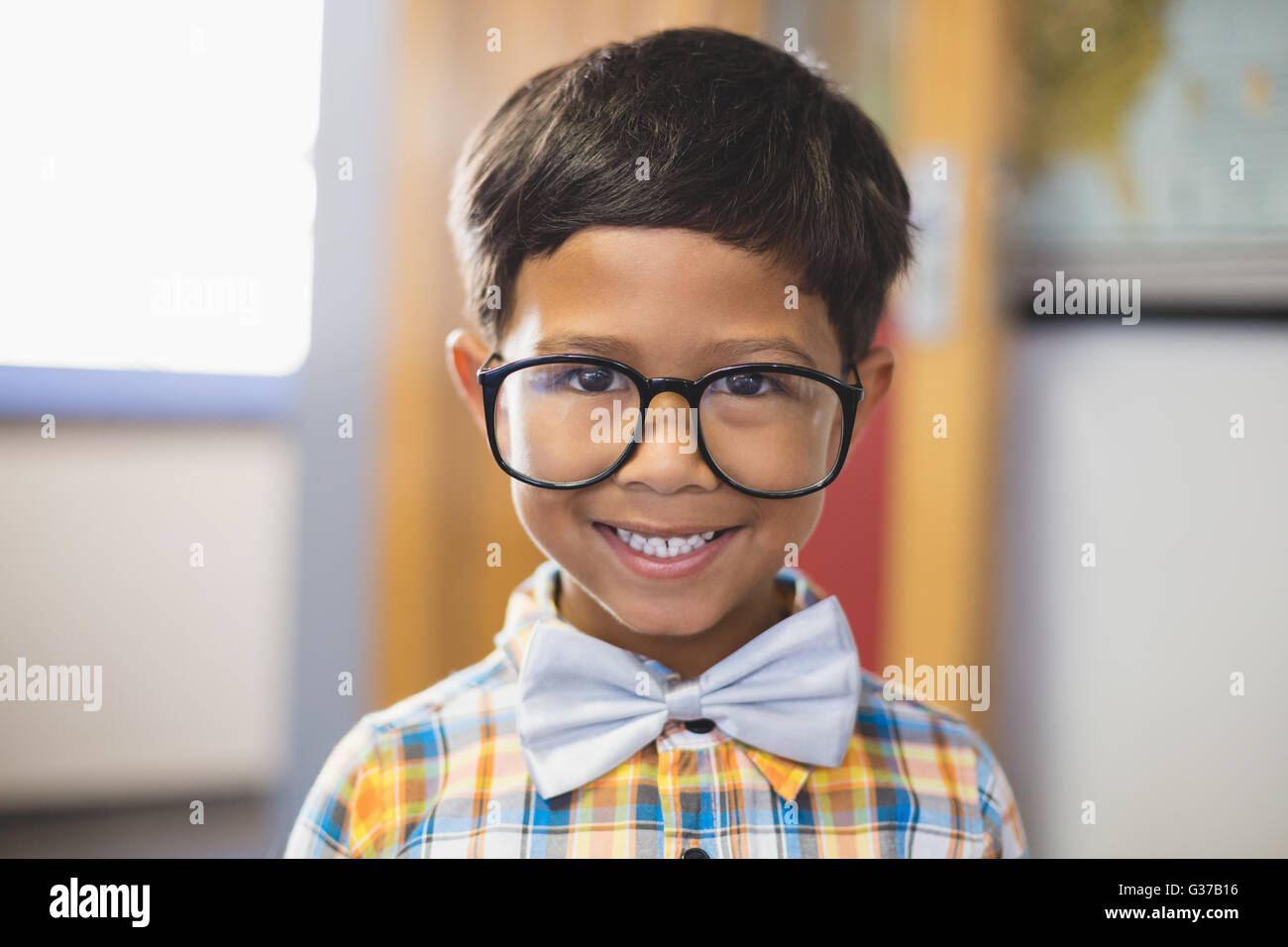 Portrait of smiling schoolboy in spectacle - Stock Image