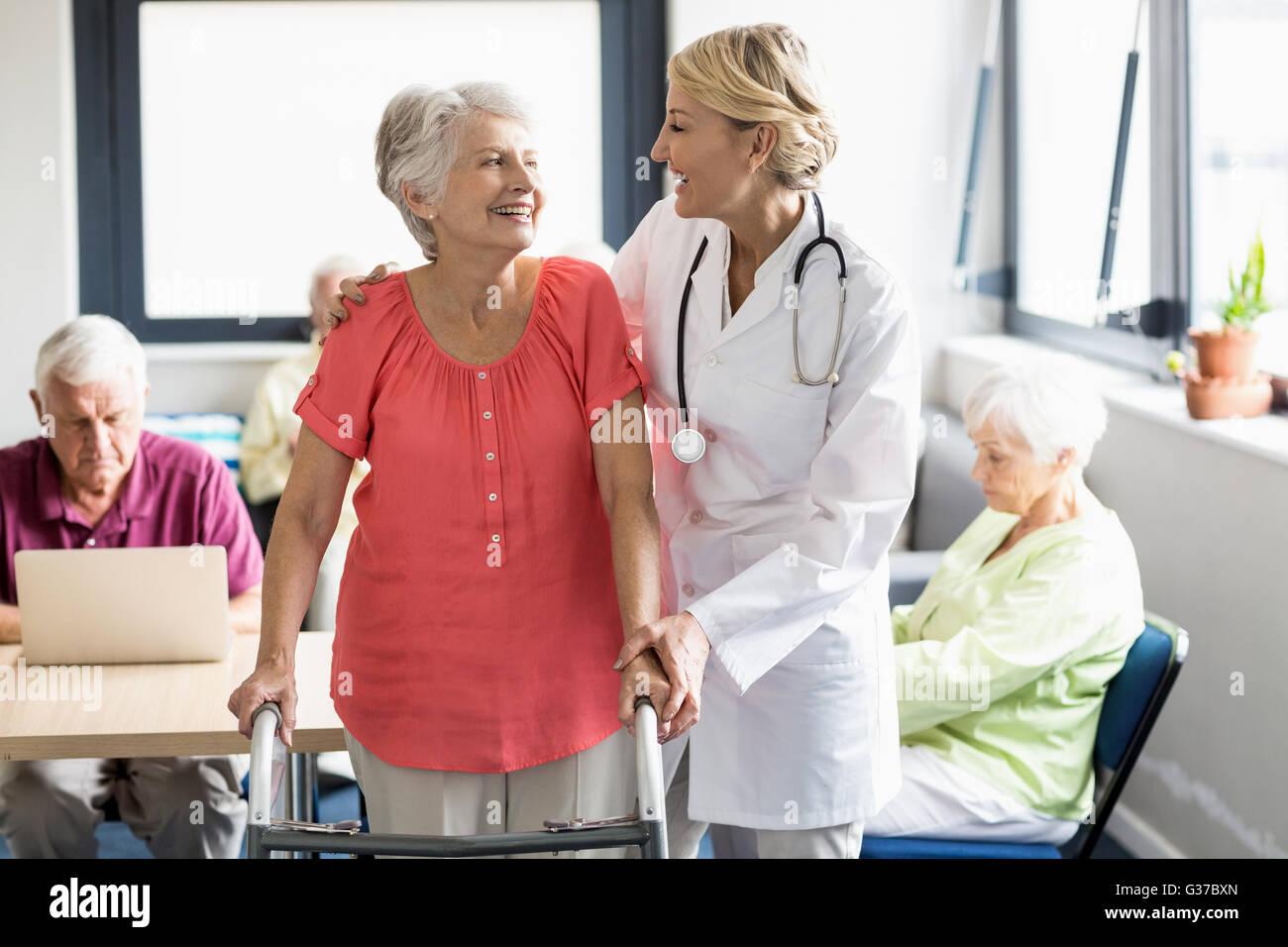 Nurse helping senior with walking aid - Stock Image