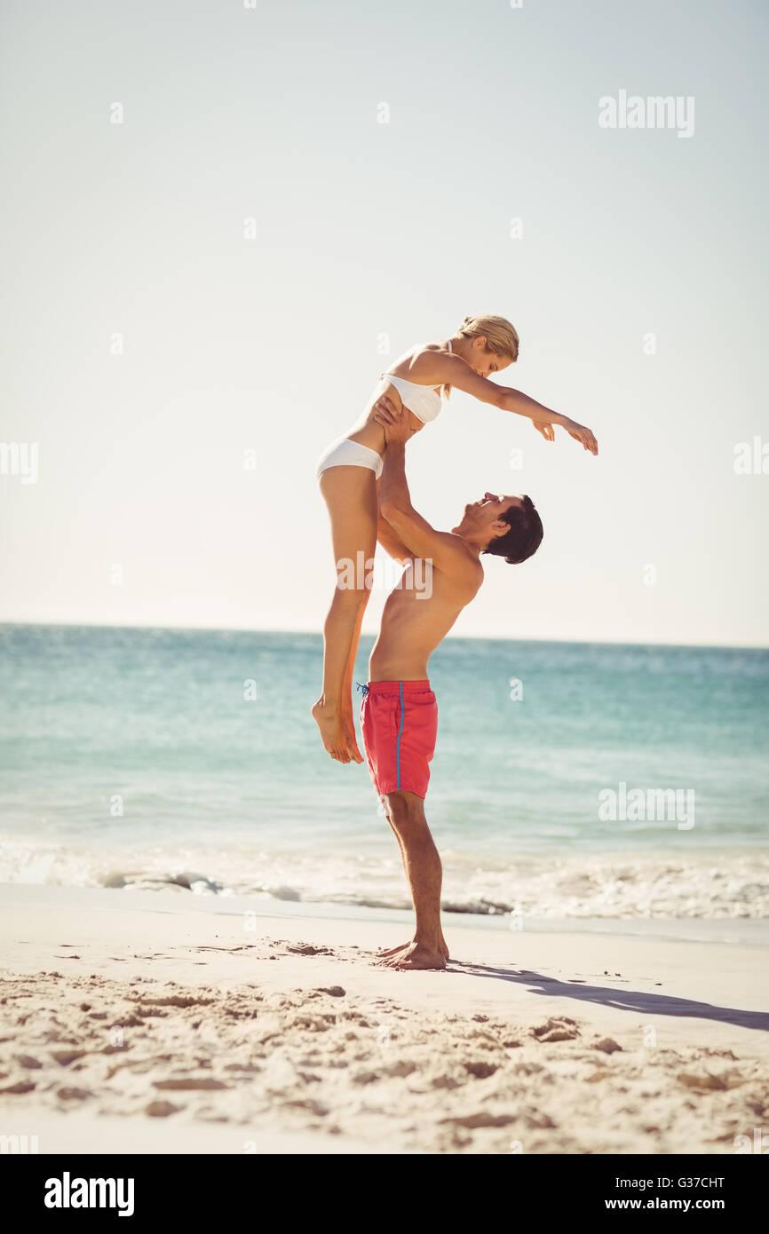Man lifting woman at beach - Stock Image