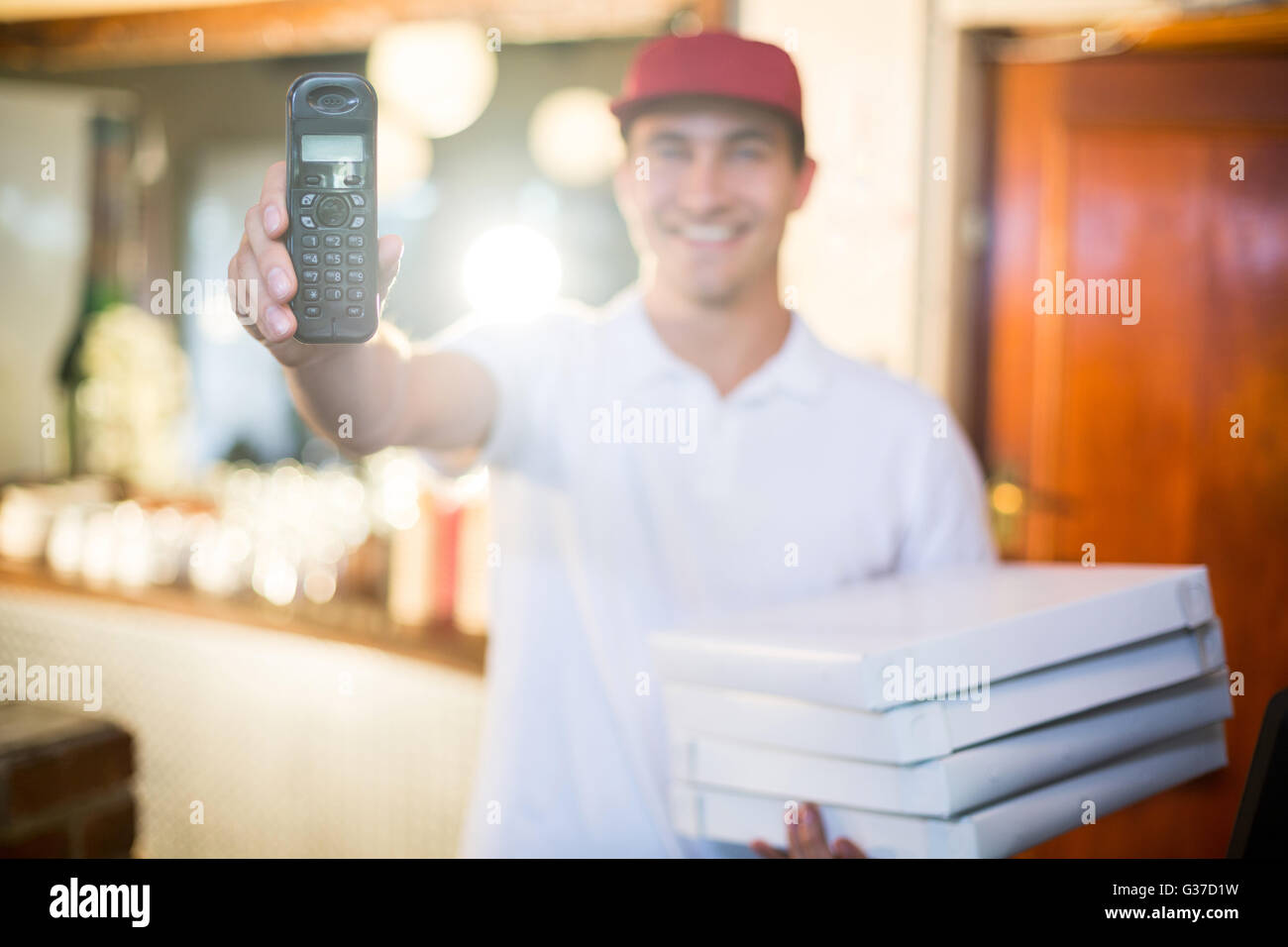 Pizza delivery man holding phone - Stock Image