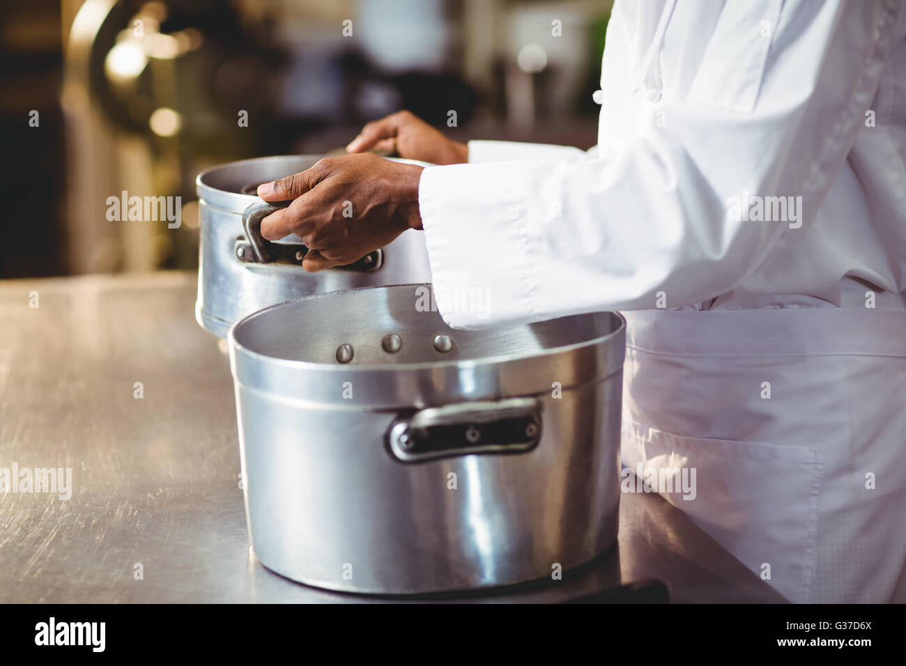 Mid section of chef holding cooking pot - Stock Image