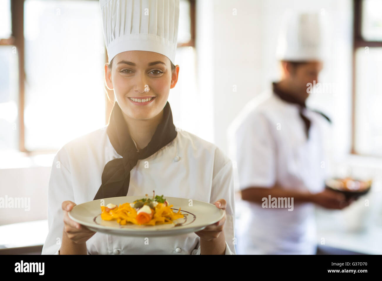 Happy head chef presenting her food - Stock Image