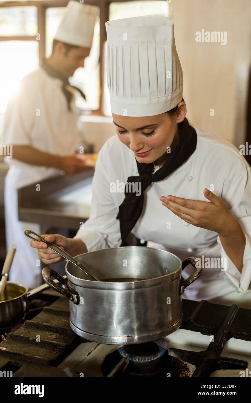 Smiling head chef stirring in cooking pot - Stock Image