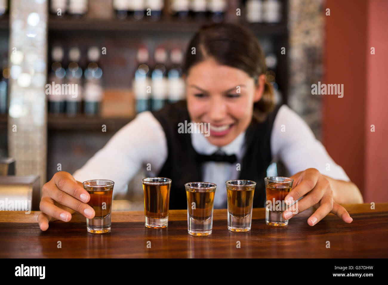Bartender placing shot glasses on bar counter - Stock Image