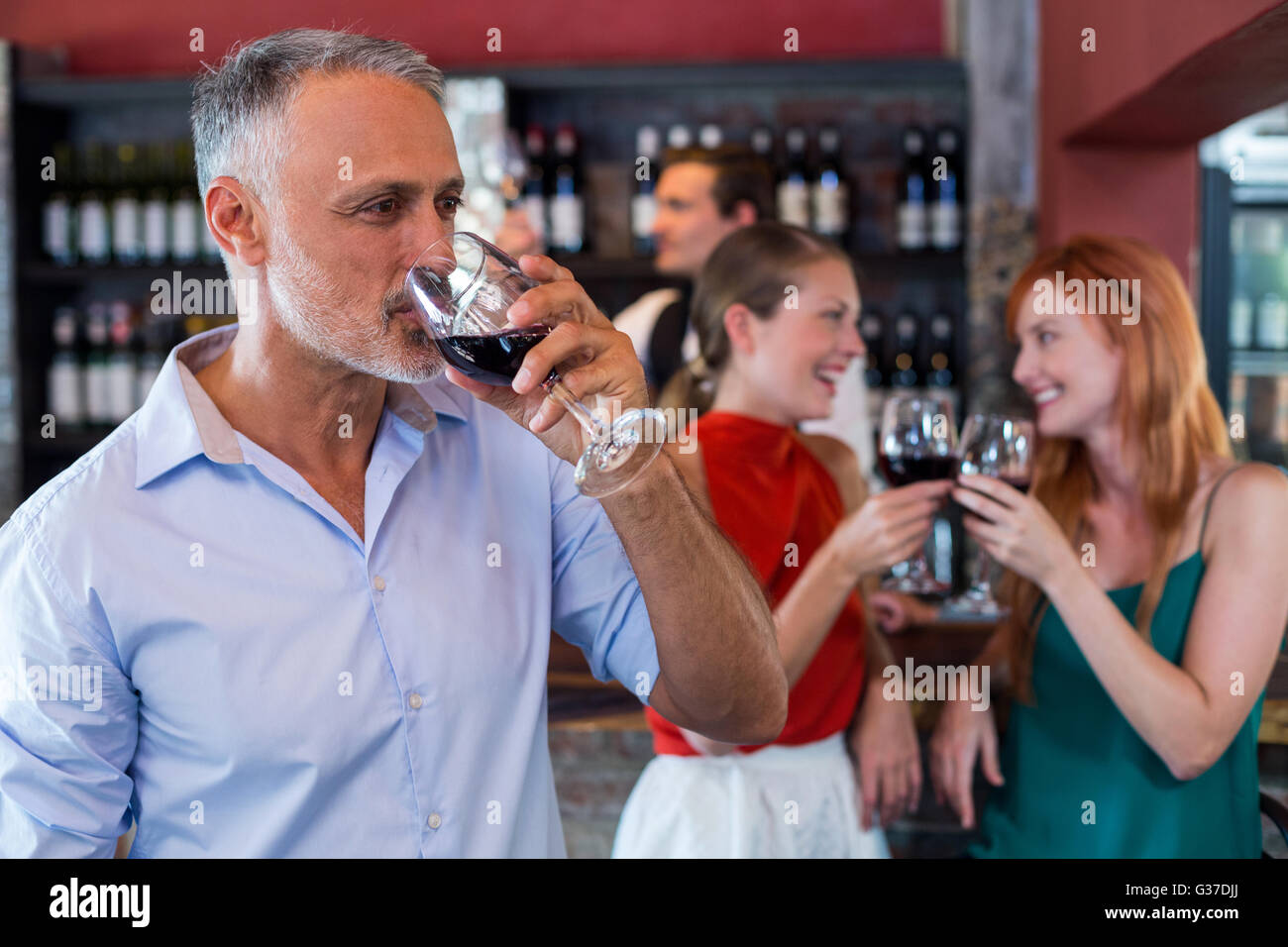 Man drinking red wine while two friends toasting the glasses in background Stock Photo