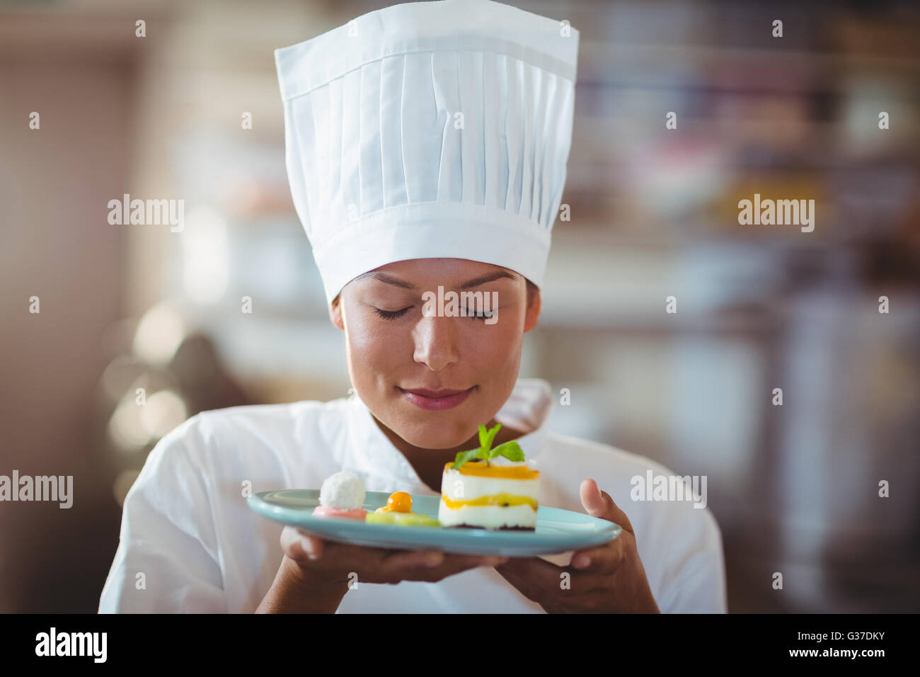 Female chef with eyes closed smelling food - Stock Image