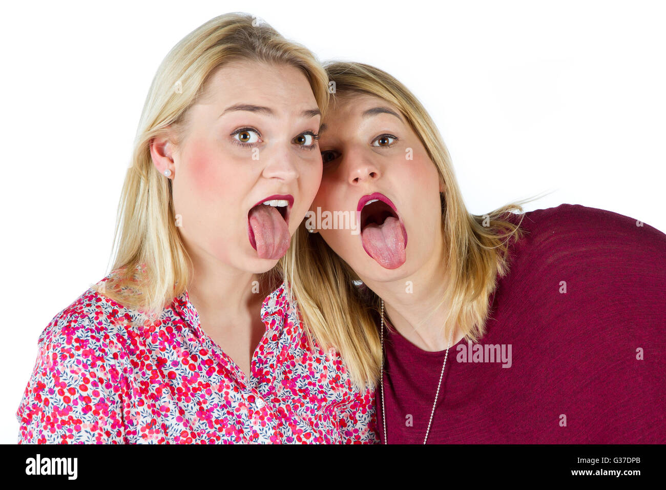 Two girls sticking tongue out - Stock Image