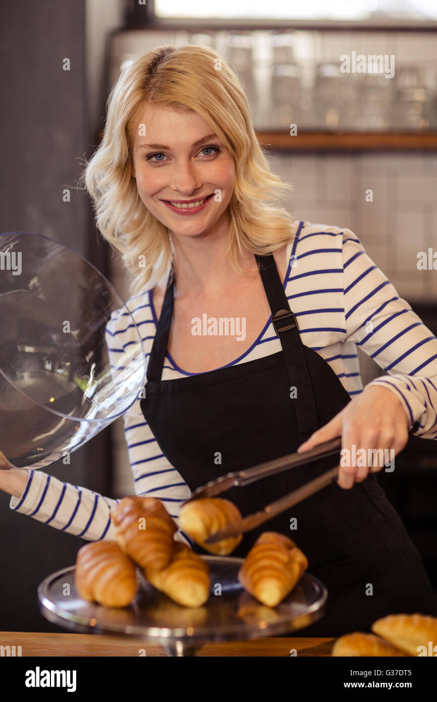 Seller picking a croissant with tongs - Stock Image