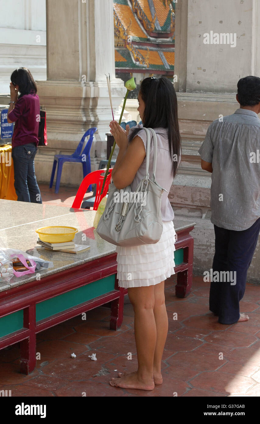 A young Thai woman prays to buddah whilst holding incense sticks in her hands at the local temple Stock Photo