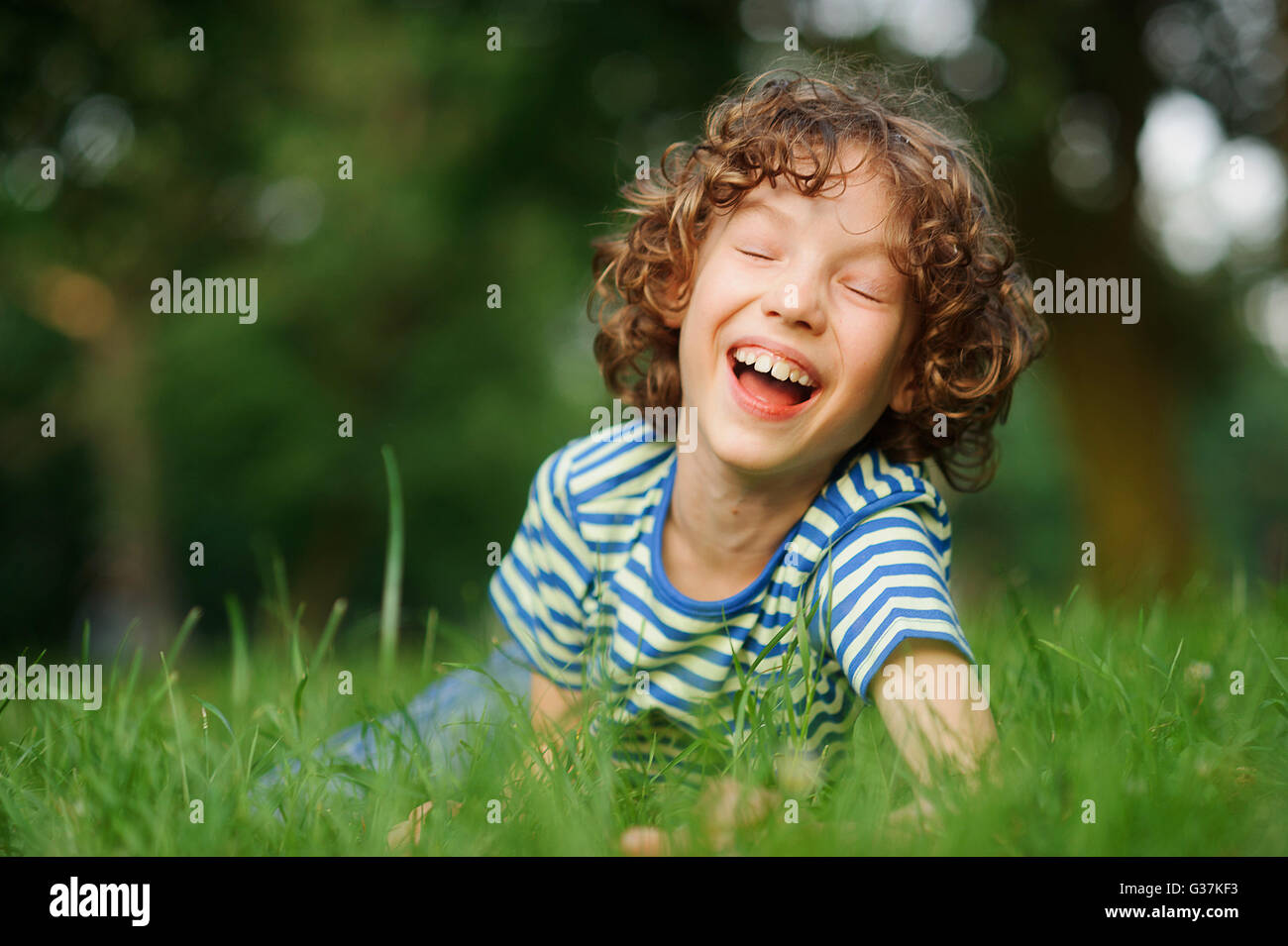 The thin boy of 8-9 years lies in a green grass and laughs loudly.He has closed eyes from pleasure.The child has - Stock Image