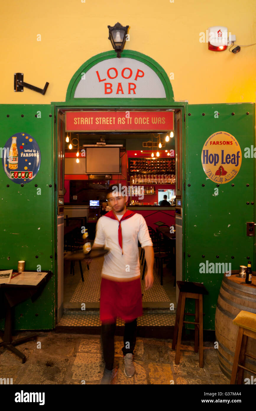 A waiter stepping out of a retro bar in Strait Street in Valletta. Stock Photo