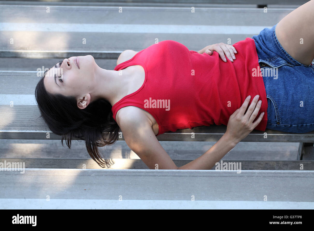 young Hispanic teen girl reclining on metal bleachers red top - Stock Image