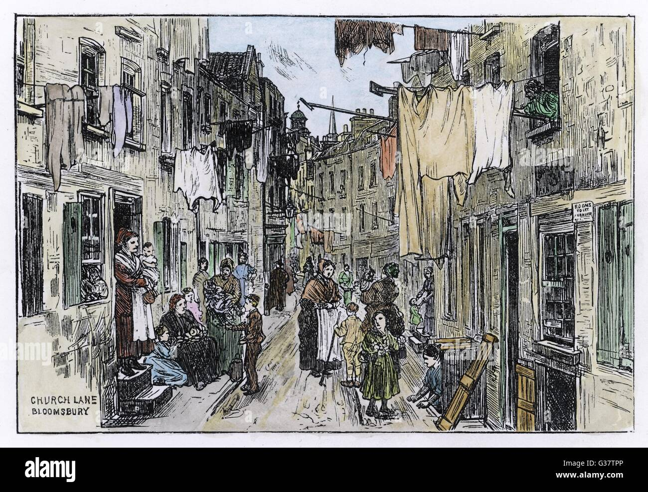 A street scene in Church Lane,  Bloomsbury, London -  mothers and children mingle in the street while washing hangs - Stock Image