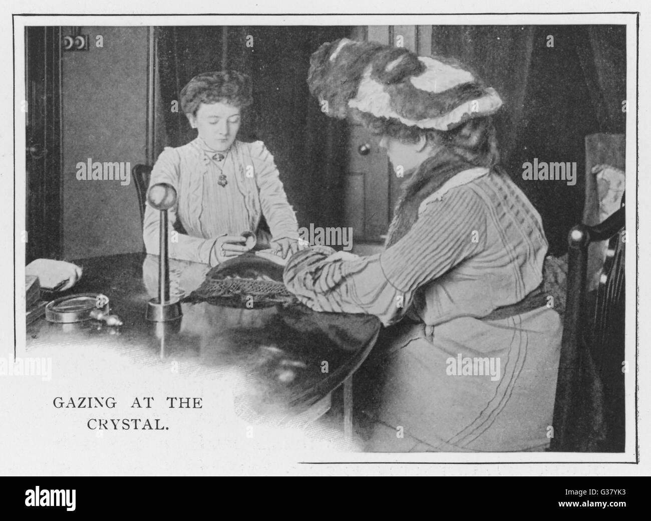 Gazing at the crystal - a client consults a London  fortune teller        Date: 1900 Stock Photo