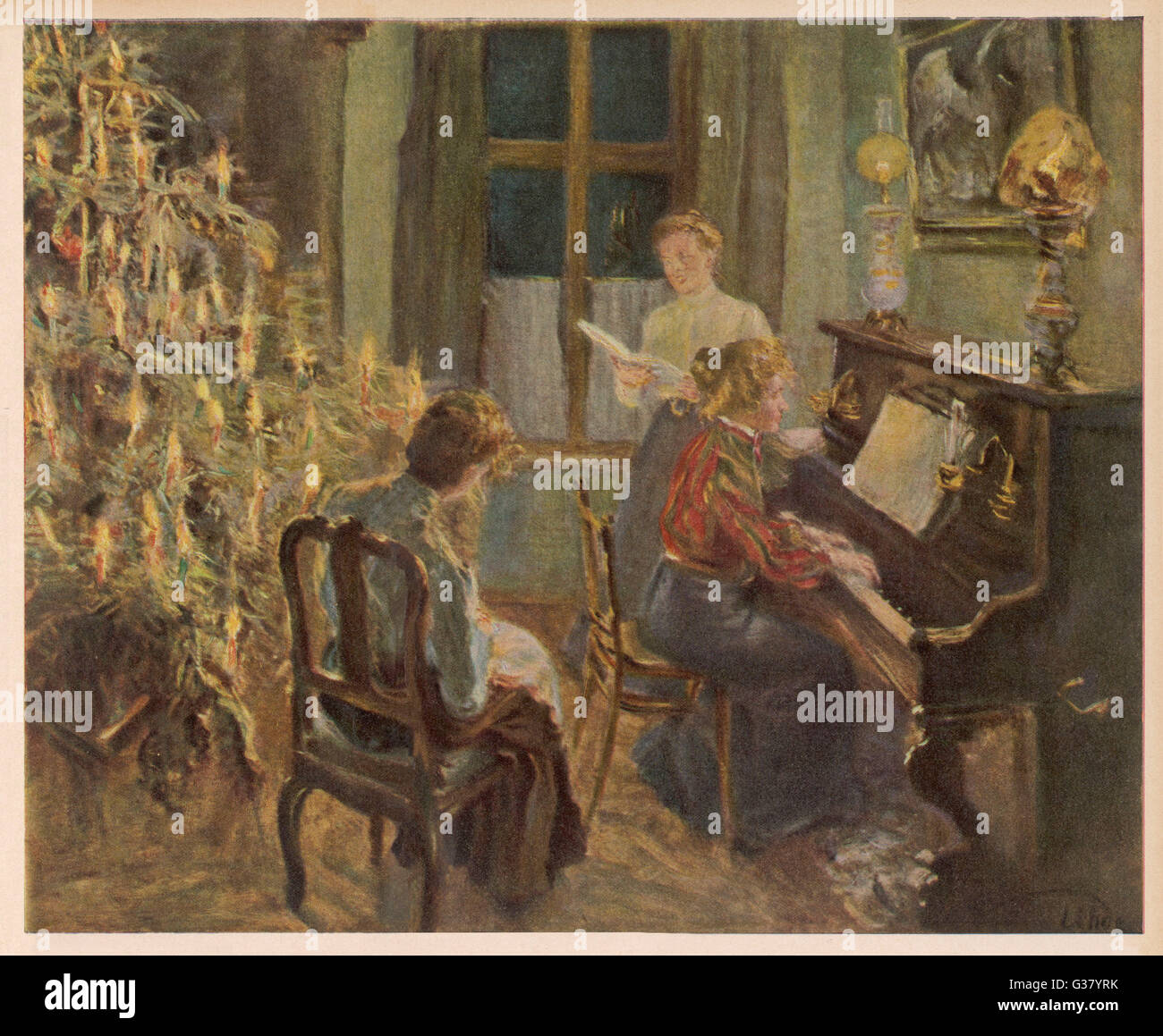 a german family sing carols by the christmas tree date 1907 stock image