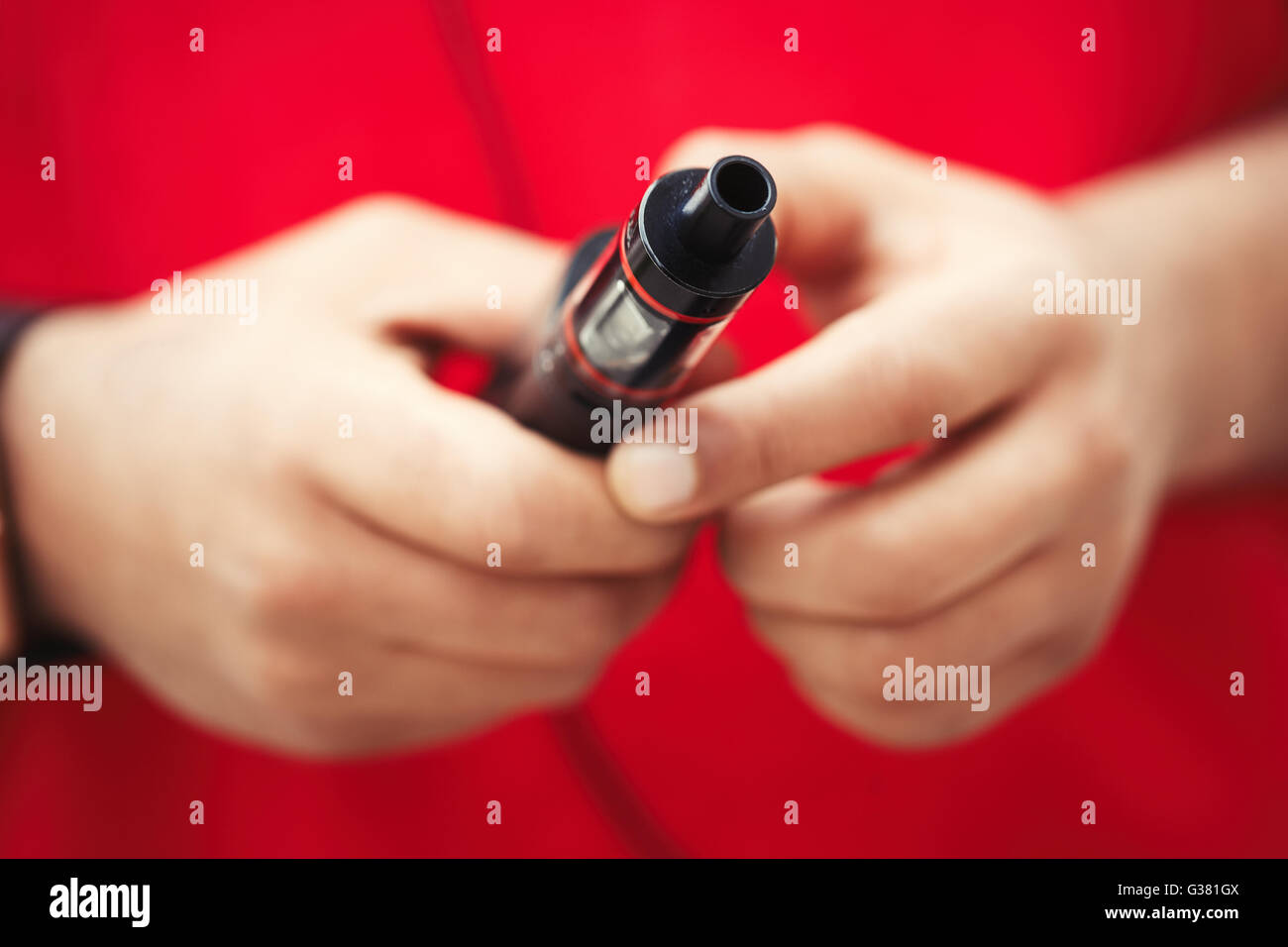 Hands of african male model using modern e-cig vaporizer device for smoking glycerine liquid tobacco with flavor. - Stock Image